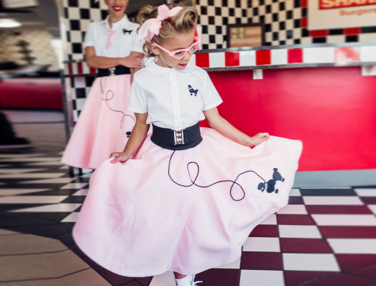 toddler wearing white and pink vintage 50's poodle skirt